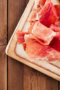 Platter of serrano jamon cured meat ciabatta chorizo on wooden table Royalty Free Stock Images