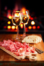 Platter of serrano jamon cured meat with cozy fireplace and wine background Royalty Free Stock Photo