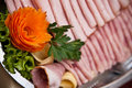 Platter of sliced ham decorative carrot in the shape a flower garnishing a buffet Royalty Free Stock Photo