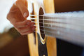 Play acoustic guitar close up of the hands Royalty Free Stock Image