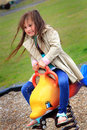 Play action a cute brave little preschool girl with long brown hair playing on a spring toy in a playground tilted view to show Stock Photos