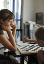 Play checkers boy and his aunt playing at a table in the house Royalty Free Stock Images