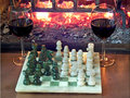 Play chess drinking red wine in front of a roaring fireplace Royalty Free Stock Photography