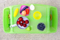 Play and eat time tray little girls with fake toy foods as well as strawberries blueberries Royalty Free Stock Images