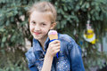 Playful attractive young girl eating ice cream grinning as she holds the cone of strawberry alongside her cheek on a sunny Stock Photos