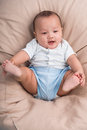 Playful baby boy one month lying in the armchair view from above Stock Photos