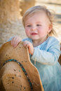 Playful baby girl with cowboy hat at the pumpkin patch adorable in a country rustic setting Stock Photography