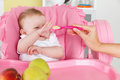 Playful baby girl is feeded by mother Royalty Free Stock Photo