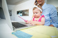 Playful baby girl sitting with mother by laptop Royalty Free Stock Photo
