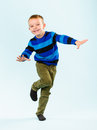 Playful boy little on studio light blue background Royalty Free Stock Images