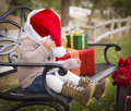 Playful child wearing santa hat sitting with christmas gifts outside happy young toddler on bench Stock Photo