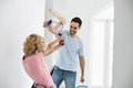 Playful couple fighting while painting new house Royalty Free Stock Photo