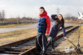 Playful couple waiting for a train with luggage standing alongside the track near rural level crossing the girl saluting as Royalty Free Stock Photography