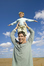 Playful father balancing son on shoulders in field Stock Images