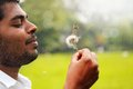 Playful, free indian man blowing dandelion flower Royalty Free Stock Photos