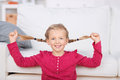Playful girl pulling her pigtails at home portrait of a in the living room Royalty Free Stock Photos