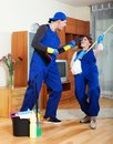 Playful housecleaners cleaning room at house Royalty Free Stock Photography