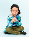 Playful little boy surprised wearing peaked cap on studio light blue background Stock Photos