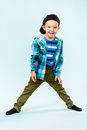 Playful little boy wearing peaked cap on studio light blue background Royalty Free Stock Photos