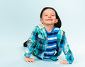 Playful little boy wearing peaked cap on studio light blue background Royalty Free Stock Photo