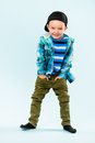 Playful little boy wearing peaked cap on studio light blue background Royalty Free Stock Image