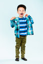 Playful little boy wearing peaked shouting on studio light blue background Royalty Free Stock Images