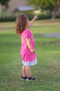 Playful little girl in the park she is pointing to something with her finger Stock Photo