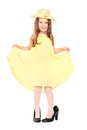 Playful little girl in trendy yellow dress and hat full length portrait of a isolated on white background Royalty Free Stock Image