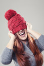 Playful pretty woman wearing a red winter beanie and smiling with bobble stuck to her nose covering the eyes Royalty Free Stock Photo