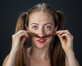 Playful redhead funny portrait of a quirky girl playing with her pigtails Royalty Free Stock Images