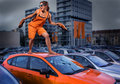 Playful stylish girl in orange overalls standing on car roof in the parking lot unique person young dressed barefoot top of Stock Images