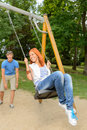 Playful teenage couple girl on swing sitting in park Royalty Free Stock Photo