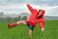 Playful teenage girl dancing in the rain on a field Stock Image