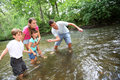 Playful time in family adults with kids throwing pebbles river Royalty Free Stock Photos