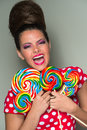Playful vivacious woman with lollipops a retro beehive hairdo wearing a red and white polka dot dress laughing as she holds a Stock Photo