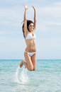 Playful woman at beach wearing white bikini jumping in water Stock Photo