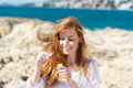 Playful woman blowing soap bubbles standing on a rocky seashore with her long red hair in the sea breeze Royalty Free Stock Photos