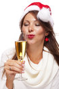 Playful woman celebrating xmas blowing a kiss wearing festive red santa hat and holding flute of champagne christmas across the Stock Photography