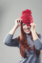 Playful woman in a knitted red beanie attractive young cap pulling it down to conceal one eye while smiling at the camera isolated Stock Photography