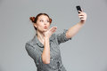 Playful woman sending kiss and making selfie with mobile phone Royalty Free Stock Photo