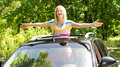 Playful woman standing in a car sunroof vivacious young blond with her arms outstretched laughing happily the sunshine Royalty Free Stock Photos