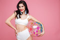 Playful woman in swimsuit holding beach ball and looking at camera Royalty Free Stock Photo