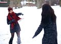 Playful women playing in the snow outdoors having fun and throwing snowballs at each other a snowy Stock Photos