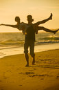 Playful young couple a clown around on the beach against a yellow sunset Royalty Free Stock Photo