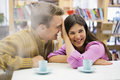 Playful young couple with coffee cups on desk in library Royalty Free Stock Photo
