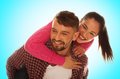 Playful young couple with woman riding piggyback fashionable women jumping to the men back and Stock Photography