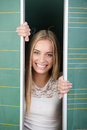 Playful young female student with a mischievous smile peeking out between two movable blackboards Royalty Free Stock Image