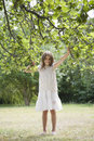 Playful young girl holding branches in garden full length portrait of Royalty Free Stock Photography