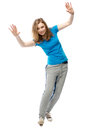 Playful young woman balancing tilted sideways beautiful with her hands raised in the air to balance her weight smiling happily at Royalty Free Stock Images