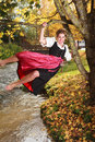 Playful young woman swinging on a tree barefoot in traditional dirndl the branches an autumn over stream laughing with happiness Royalty Free Stock Photos
